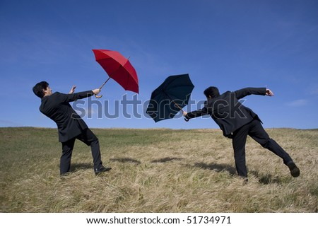 Business concept with two men holding umbrellas for protection - stock photo