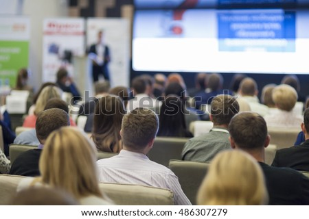 Business Concepts. People At the Conference Listening to Speaker On Stage in Front of Huge Screen with Charts.Horizontal Image Orientation