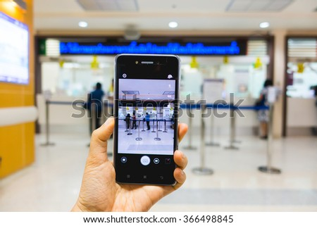 Business conceptual- Focused on left hand holding mobile with taking picture at hospital interior with blurred background