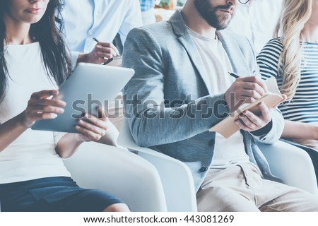 Business conference. Close-up of young people sitting on conference together and making notes - stock photo