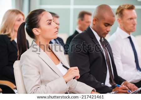 Business conference. Group of business people in formalwear sitting at the chairs in conference hall and writing something gin their note pads  - stock photo