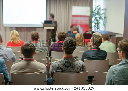 business conference - people sitting rare and speaker near the screen - stock photo