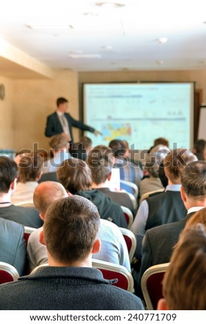 business conference. people sitting rear and speaker explaining - stock photo