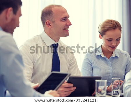 business, conference, people, technology and teamwork concept - smiling businessmen and businesswoman with tablet pc computer meeting in office - stock photo