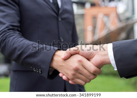 Business confidence and agreement. Close up of handshake of two successful businessmen. Outdoors business agreement concept - stock photo