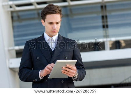 Business confidence and elegance. Portrait of confident and motivated businessman. Man is standing in formal suit with tablet and working on current project. Outdoor business concept - stock photo