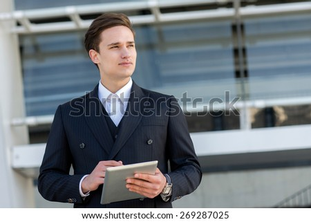 Business confidence and elegance. Portrait of confident and motivated businessman. Man is standing in formal suit with tablet and working on current project. Outdoor business concept