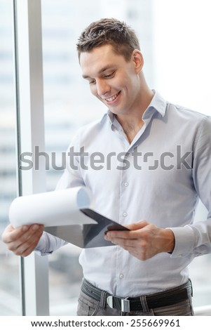 business, construction and office concept - smiling businessman with clipboard in office - stock photo