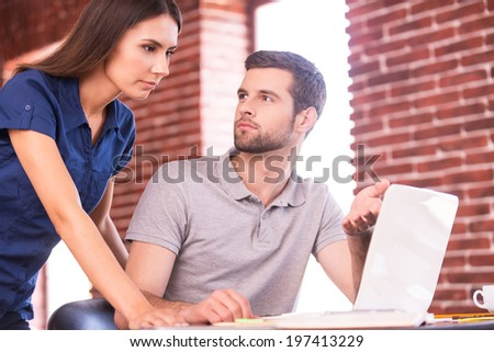 Business consulting. Handsome young man sitting at his working place and pointing computer while confident woman standing close to him - stock photo