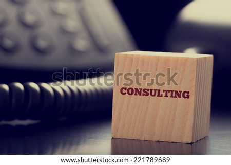 Business Consulting Themed Image of Wooden Block in front of Telephone. - stock photo
