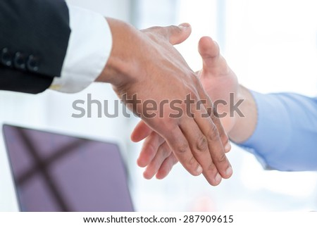 Business contract and a handshake. Two Confident businessman sitting at the negotiating table in the office and shaking hands close-up view of hands. Business people dressed in formal wear - stock photo