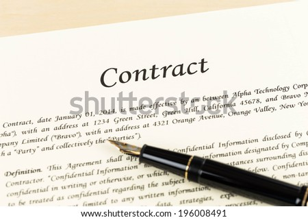 Business contract document on cream color paper with pen