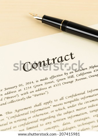 Business contract document on cream color paper with pen and glasses