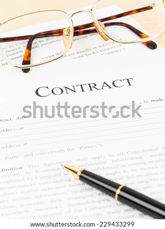 Business contract document with pen and glasses - stock photo