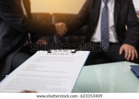 business contract on background of two employees handshaking