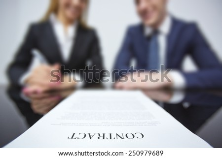 Business contract on workplace with two colleagues on background - stock photo