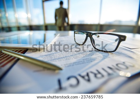 Business contract with pen, eyeglasses and touchpad on it and businessman on background