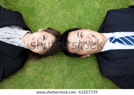 business couple.happy  businessman and woman Lay on the grass - stock photo