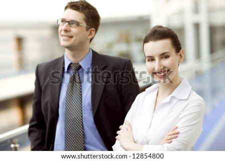 Business couple portrait - young man and woman on modern office corridor - stock photo