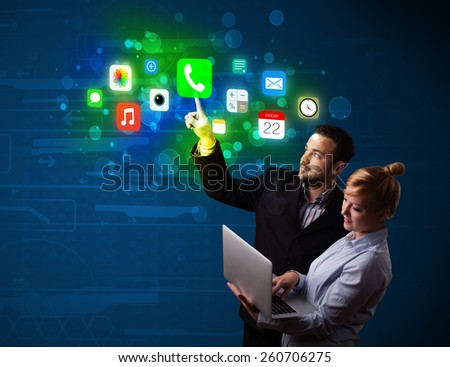 Business couple pressing colorful mobile app icons with bokeh background
