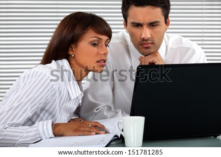 Business couple sitting at a laptop - stock photo