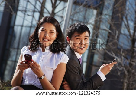 Business couple sitting on the bench chatting with mobile phone