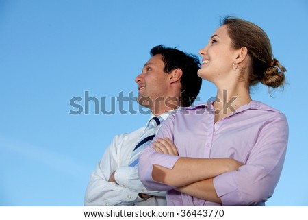 Business couple smiling and looking at the sky - stock photo