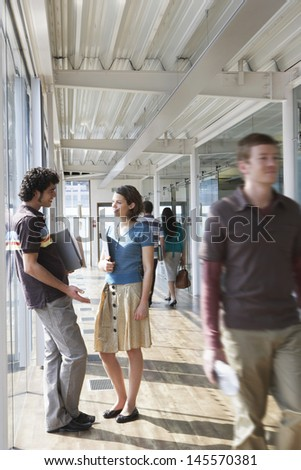 Business couple standing in corridor as colleagues pass by