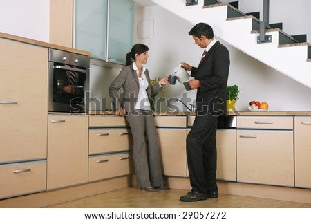 Business-couple standing in kitchen with cups - stock photo