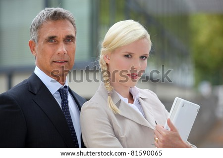 Business couple standing outside - stock photo
