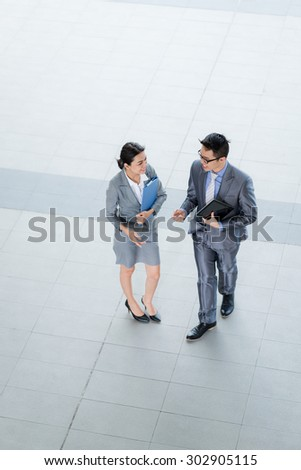 Business couple talking outdoors, view from above