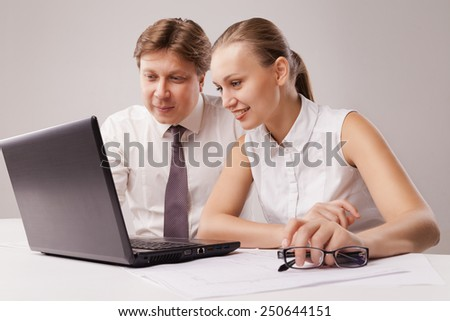 Business couple using laptop. Isolated over white background. - stock photo