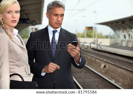 Business couple waiting for a train - stock photo