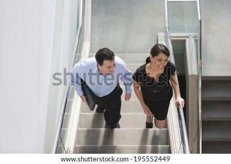 Business couple walking up stairs together - stock photo