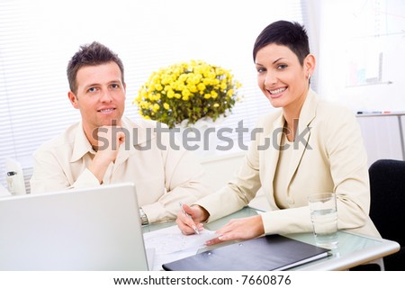 Business couple working at office, smiling.