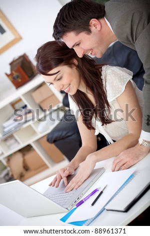 Business couple working at the office looking happy - stock photo