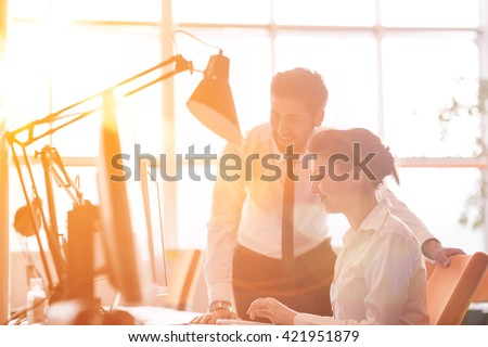 business couple working together on project at modern startup office. Early morning scene with sun flare in background