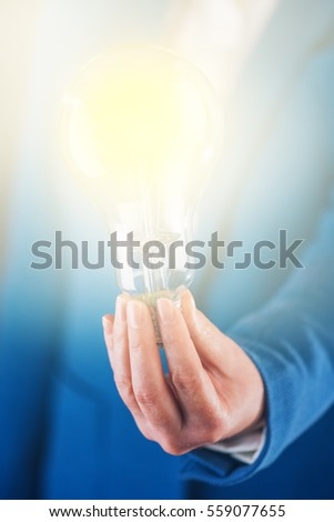 Business creativity, light bulb in hands of a businesswoman shining bright for brainstorming, innovation and new ideas concept