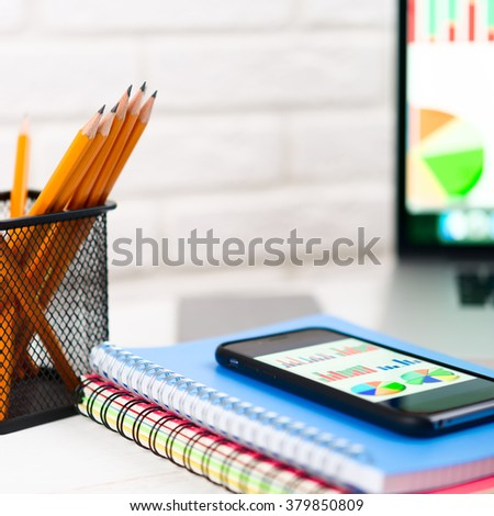 Business data on the smartphone display. Workplace with notebook , laptop, pencils on a light background. - stock photo