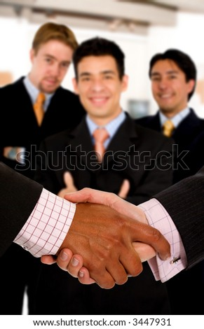 Business deal at the office - team of businessmen behind a handshake - stock photo
