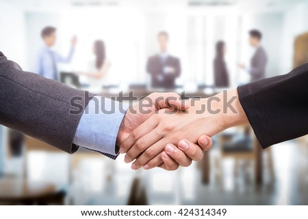 Business deal with handshake and business people at office on background.