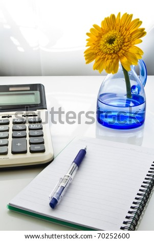 Business desk with bright yellow flower in blue vase