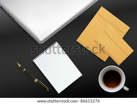 business desktop with laptop, notepad, envelops and mug of tea - stock photo