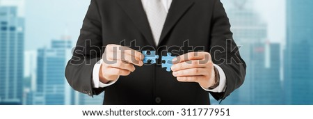 business, development and people concept - close up of man trying to connect puzzle pieces over city background - stock photo