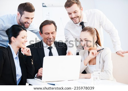 Business discussion. Group of confident business people in formalwear sitting at the table together and discussing something while looking at the laptop  - stock photo