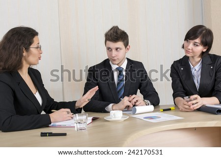 Business discussion. Group of young businesspeople discuss the idea with the charts and other paperwork on the table. - stock photo