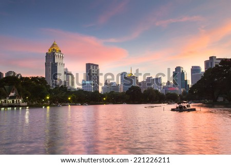 Business district cityscape from a park with Twilight Time from Lumpini Park, Bangkok, Thailand - stock photo