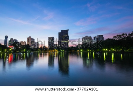 Business district cityscape from the lumpini park at twilight time, Bangkok Thailand. The sky is blue.
