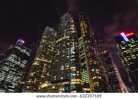 Business District, Singapore - January 05, 2015: Office buildings at the business district in Singapore at night with light trails from cars on the street.