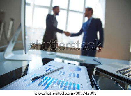 Business document at workplace with business partners handshaking on background - stock photo